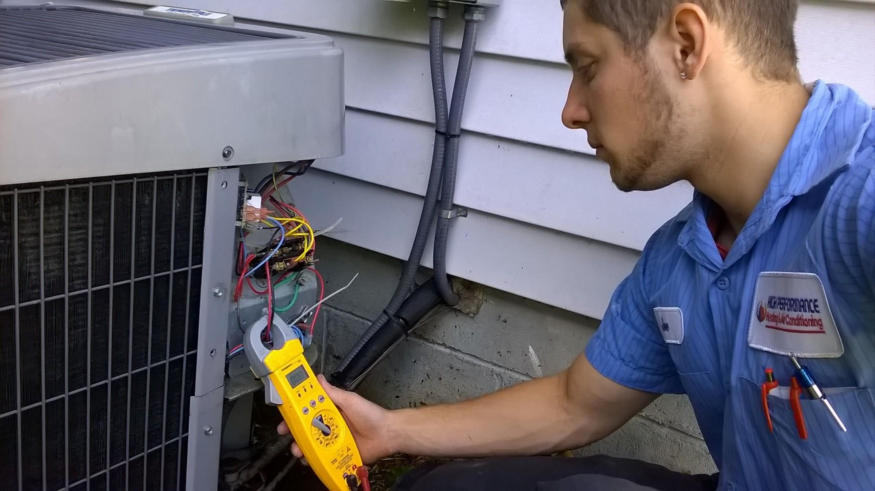 HVAC Technician checking the power consumption of a Air Conditioning unit while performing hvac service.